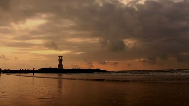 Lighthouse with waves at sunset.
