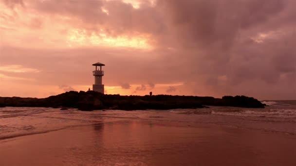 Maják s vlnami při západu slunce.