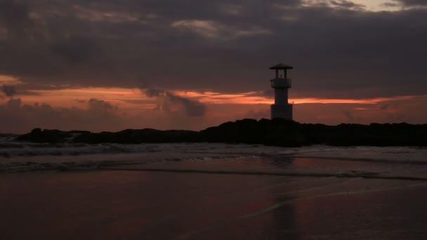 Maják s vlnami při západu slunce