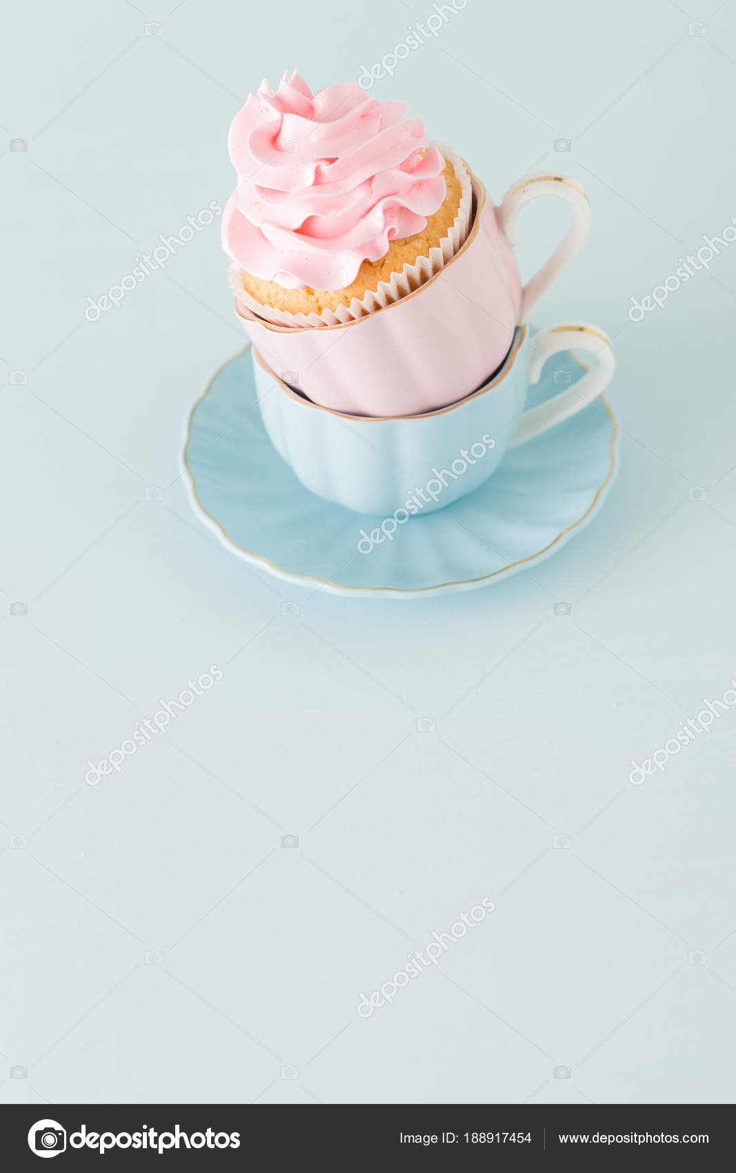 Cupcake with gentle pink cream decoration in two cups on blue pastel background stock photo - Creme decoration cupcake ...