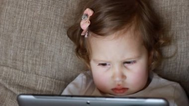 Funny child looks at the screen and plays downloaded application on tablet laptop, computer A little cute girl lies in sofa in a living room, looking cartoon and playing the game. close-up