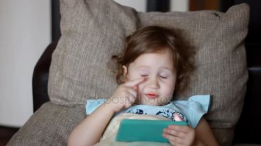 Funny child looks at the phone screen and plays downloaded application on a smart phone close-up. A little cute girl lies in sofa in a living room, looking cartoon and playing the game.