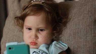 Funny child looks at the phone screen and plays downloaded application on a smart phone close-up. A little cute girl lies in sofa in a living room, looking cartoon and playing the game. Close-up.