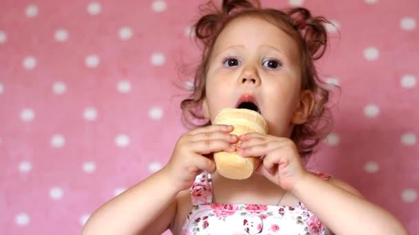 Legrační šťastný a krásný dítě close-up jí zmrzlinu s emocí a radosti, roztomilá holčička úsměvy a raduje se. Koncept dětství. Smích dítěte