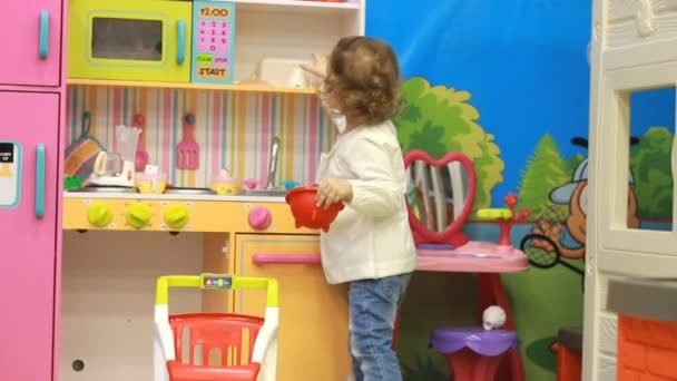 Funny cute child on the playground plays different games. Little girl and entertainment and development of preschool children. Kindergarten and toys for kids. Kids Kitchen