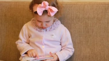 Funny child looks at the phone screen and plays downloaded application on a smart phone close-up. A little cute girl lies in sofa in a living room, looking cartoon and playing the game