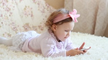 Child Looks cartoons and plays downloaded application on a smart phone close-up. A little cute funny girl lies in bed under the blanket and looks at the white phone screen.