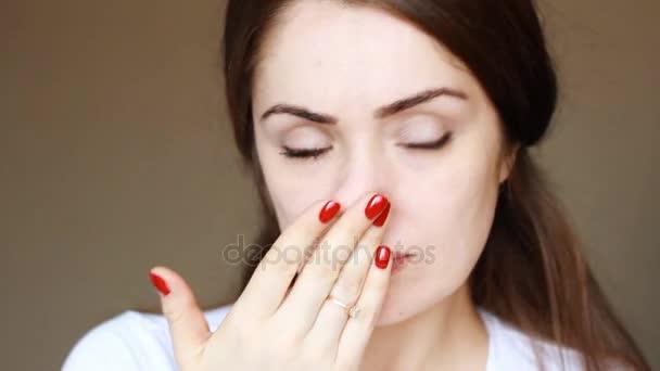 Portrét mladé dívky close-up, kdo podrbe se na nose. Rýma, alergie, nudle u nosu, kýchání, virus, studené