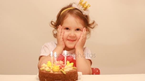 Malá roztomilá holka dělá přání a sfoukne svíčky na narozeninový dort na večírku. Legrační šťastné dítě. Koncept svátek dětí. 3 roky
