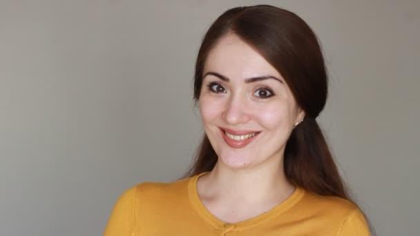 Šťastný obličej mladé ženy. Portrét krásné bruneta dívka usmívá a vypadá na kameru, makro portrét. Hravý úsměv. Closeup