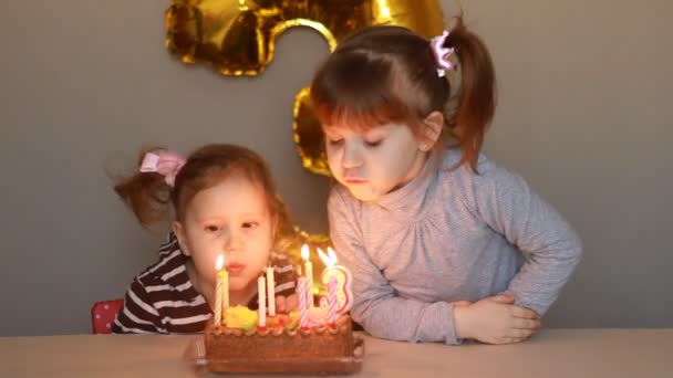 Little girls blows out candles on birthday cake at party. Funny happy kids. The concept of a childrens holiday. 3 years