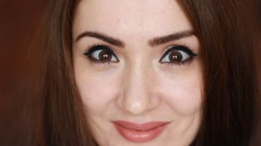 Close-up portrait of a beautiful young brunette woman who is smiling, sends an air kiss and winks looking at the camera. Face of an attractive girl with brown eyes on a dark background.