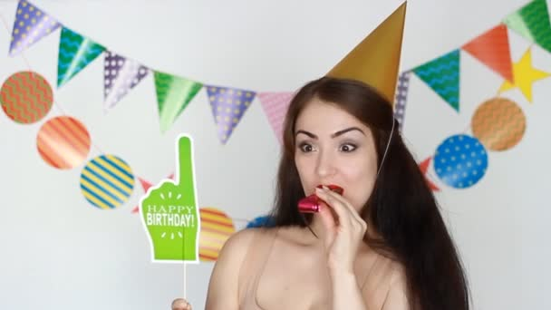 La ragazza divertente sorrisi e soffiaggio corni del partito. Buon Compleanno. Decorazione per la celebrazione