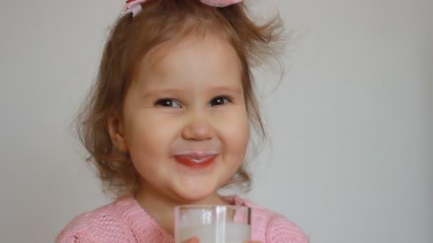 Dítě pije mléko pití - kefír, smoothie, koktejly, jogurt. Pěkná malá holčička drží sklenici v ruce. Portrét detail