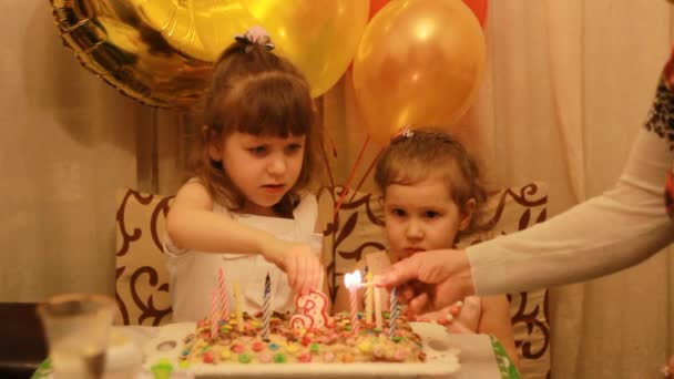 Little cute girls and on birthday dessert at party. Funny happy kids. The concept of a childrens holiday. 3 years. Light candles on the cake.