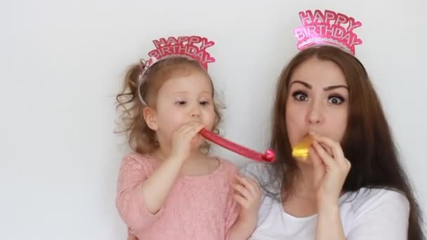 Happy Birthday Mother And Daughter Smile Have Fun Laugh And Celebrate Blowing Party Horns A Woman And Her Child Close Up Portrait On White Background