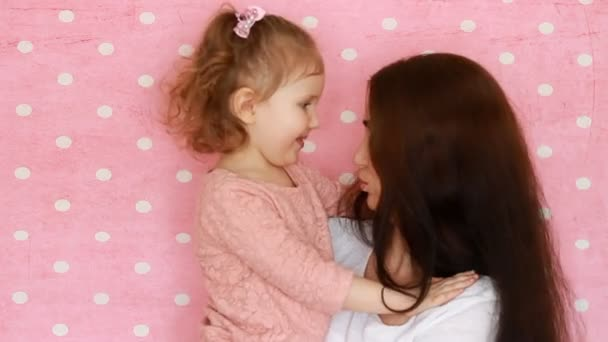 Mother and daughter embrace, smiles, have fun, laugh and kissed. Close-up portrait young woman and her child on pink background.