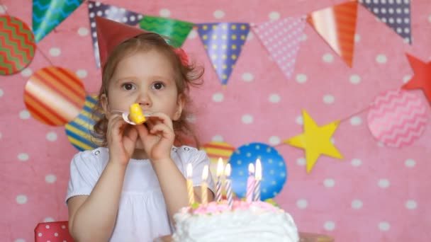 Happy birthday. Cute child make a wish and blows out candles on cake at party. Funny little girl and a holiday. pink background