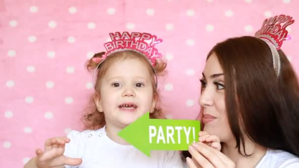 Party. Happy birthday. Mother and daughter play together and laugh.The concept of a holiday, decor for celebration. Portrait of a young woman and a child close-up