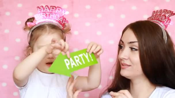 Party. Family - mother and daughter play together and laugh. Decor for celebration. Happy birthday. Portrait of a young woman and a child close-up