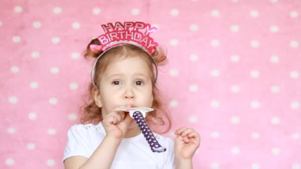 Happy birthday. Party. Celebration. Funny child blowing horn, smiling, have fun, laugh, holidays and celebrate. Close-up portrait cute girl on pink background. Copyspace.