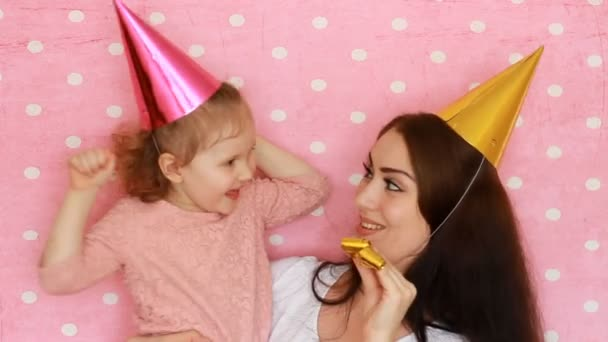 Happy Birthday. Woman and child in holiday caps blowing horns, smiling and laughing. Mother and daughter having fun and embracing on a pink background.