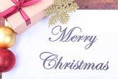 Text Veselé Vánoce na papíře s mnoha míčky a dárkové krabičky