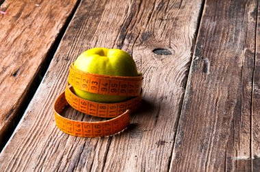 Green apple wrapped with tape measure tailor. Wooden background. Copyspace