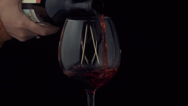 wine is pouring from a bottle into a glass in slow motion