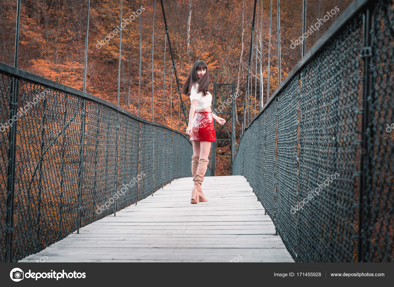 2299c0ed86a Όμορφη Καυκάσιος Ευρωπαϊκή κορίτσι με κόκκινη φούστα, ψηλές μπότες και  λευκό πάνω σε μια γέφυρα