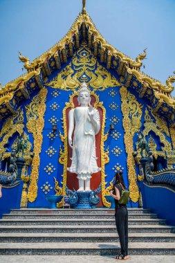 Beautiful young Caucasian woman in a Buddhist Blue Temple (Wat Rong Suea Ten) in Chiang Mai, Thailand