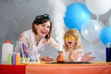 Crazy professor woman conducting chemical experiments in the company of a little smiling girl.