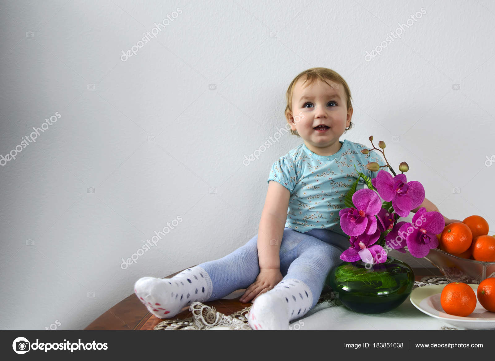 little cute baby girl sitting on a table next to a flower of orc