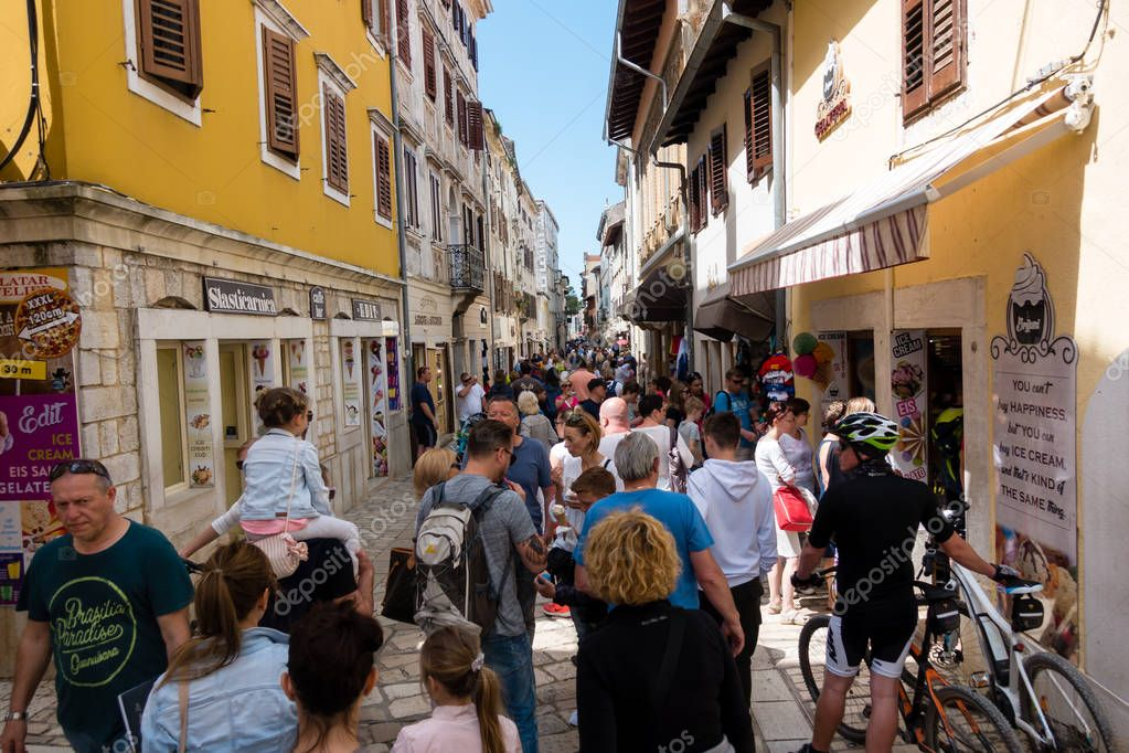 Tourists walking through the main street of medieval town of Porec, Croatia