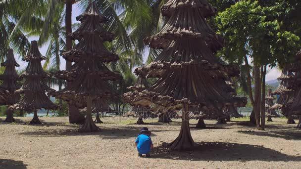 Batole chlapce, který seděl pod vánoční stromky z recyklovaných materiálů ze starých palmové ratolesti