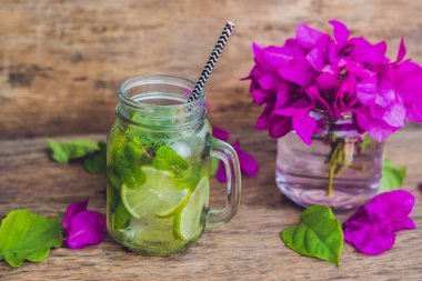 Spring purple flowers and spring mojito drink on an old wooden background