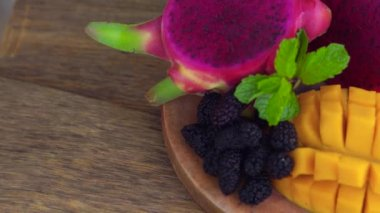 Sliced dragon fruit and mango on an old wooden background