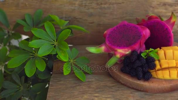 Dračí ovoce a mango nakrájené na staré dřevěné pozadí