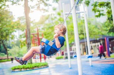 little boy on a swing in the park.