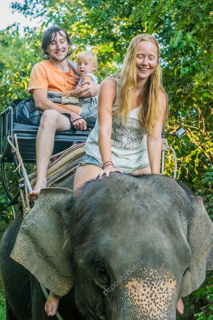 Happy family riding on an elephant