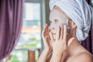 woman doing facial mask sheet