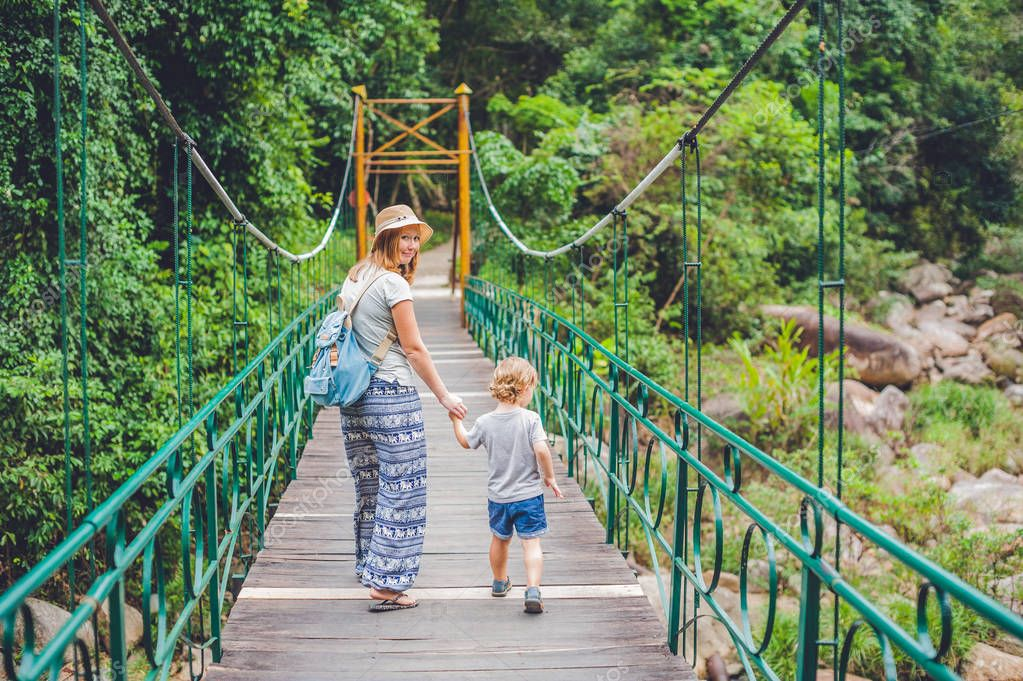 Mother and son are going on a suspension bridge