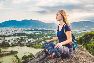 Young woman meditating over ancient city