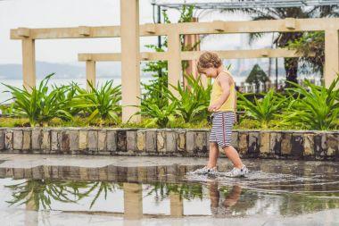 Little boy running  through a puddle.