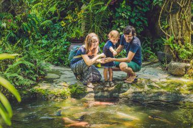 happy family feeding colorful Catfish