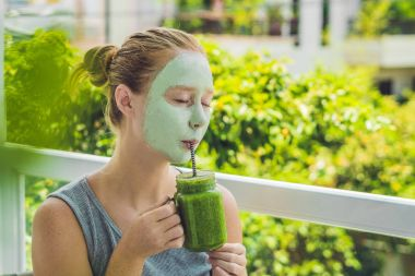 Woman applying Facial green clay Mask