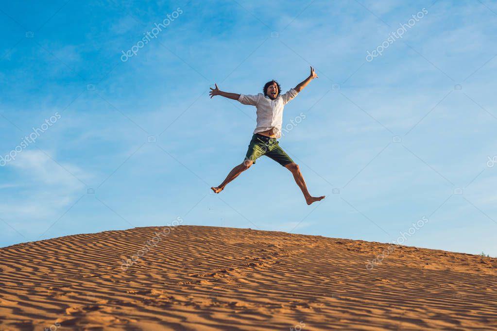 man jumping barefoot on sand