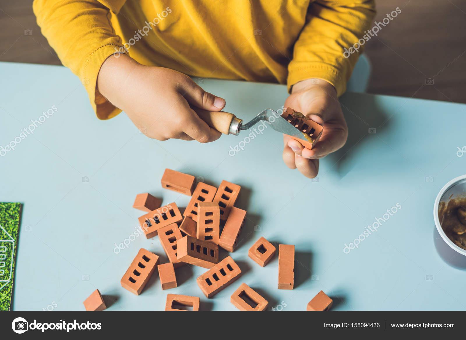 Närbild av barnets händer spelar med riktigt små Lerategelstenar vid bordet.  Småbarn har kul och bygga ur verkliga små lerategelstenar. Tidigt lärande. 19e6ef311a05e
