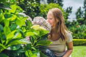 Young woman with hydrangea blooming
