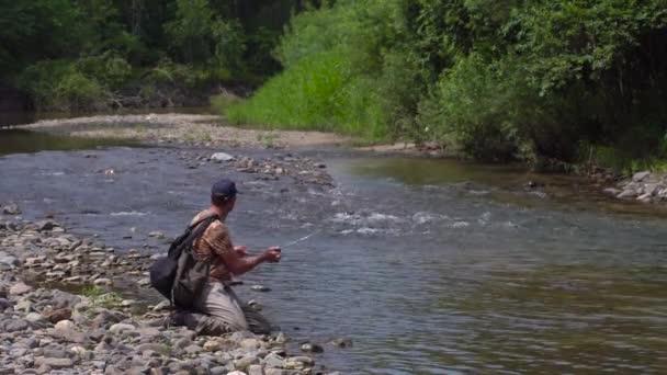 Человек, рыбалка на горной реке с ультралайт спиннинг с помощью ...